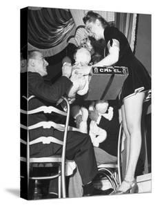 Cigarette Girl Playing with a Stuffed Animal with a Patron at the Opening of the Diamond Horseshoe by John Phillips