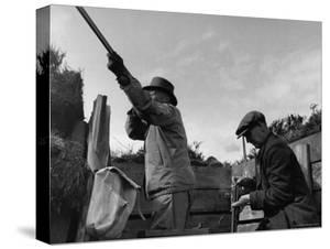 Herbert Lee Pratt Firing His Gun Toward a Grouse While the Loader Reloads Ammunition by John Phillips