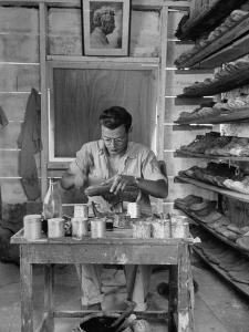 Shoemaker Sitting in His Shop Working on a Pair of Old Work Shoes by John Phillips