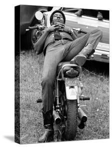 African American Man Relaxing on His Motocycle During Motorcycle Races near Detroit, Michigan by John Shearer