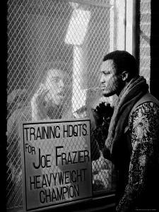 Boxer Muhammad Ali Taunting Rival Joe Frazier at Frazier's Training Headquarters by John Shearer