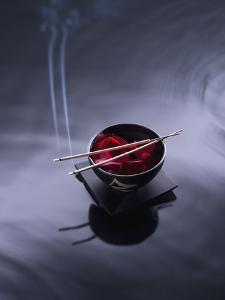 Burning incense on top of bowl of petals by John Smith