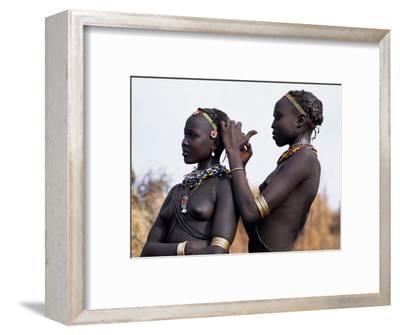 Dassanech Girl Braids Her Sister's Hair at Her Village in the Omo Delta
