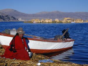 Indian Woman from the Uros or Floating Reed Islands of Lake Titicaca, Washes Her Pans in the Water  by John Warburton-lee