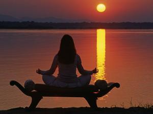 Yoga on a Saddle Bench Watching the Sun Go Down across the Zambesi River, Zambia by John Warburton-lee