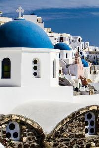Oia, Greece. Row of Greek Orthodox Churches with blue domes. by Jolly Sienda