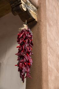 Santa Fe, New Mexico. Long, red chili, hanging from a wooden corbel and stucco wall by Jolly Sienda