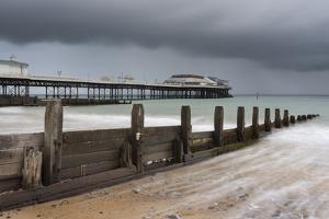 A stormy sky over the beach and pier at Cromer, Norfolk, England, United Kingdom, Europe by Jon Gibbs