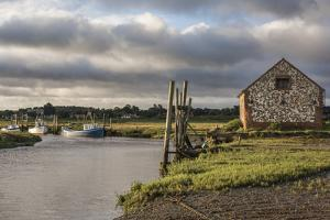 A view of boats moored in the creek at Thornham, Norfolk, England, United Kingdom, Europe by Jon Gibbs