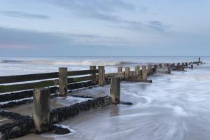 Incoming waves hitting a groyne at Walcott, Norfolk, England, United Kingdom, Europe by Jon Gibbs