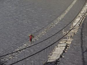 A Hunzukut Woman Crosses a Footbridge over the Hunza River, Constructed of Tied Juniper Branches by Jonathan Blair