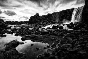 Heavy Clouds Over Oxararfoss Waterfall, and the Rocky Landscape Around It by Jonathan Irish