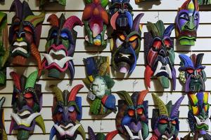 Colorful Carved Wooden Masks Hang for Sale on a Wall in a Tourist Shop in Costa Rica by Jonathan Kingston