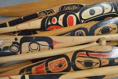 Hand-Painted Haida Canoe Paddles Stacked in the Bottom of a Small Boat