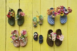 Shoes Nailed to a Bright Yellow Wall Act as Containers for Artificial Flowers by Jonathan Kingston