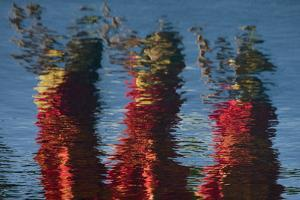 The Reflection of Hula Dancers, Dressed in Red, Dancing on the Edge of a Pool in Molokai by Jonathan Kingston