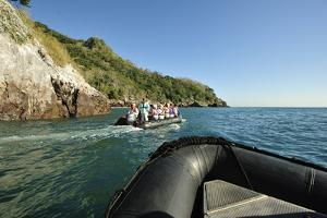 Tourists in a Small Inflatable Boat Explore the Coastline of Bona Island by Jonathan Kingston