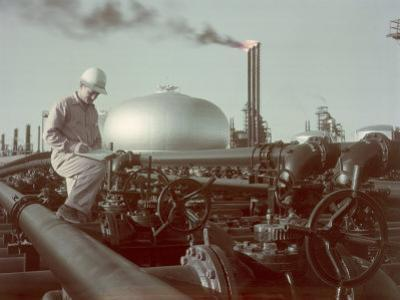 Oil Worker Records Data While Standing Amid Refinery Equipment by Joseph Baylor Roberts