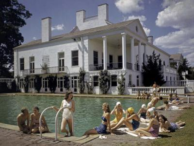People Sunbathe Beside a Swimming Pool at Charlotte Country Club