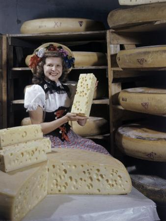 Woman Poses with Large Wheels and Chunks of Swiss Cheese