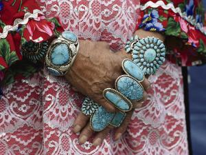 Heirloom Rings and Bracelets Lie Thick on the Arms and Hands of a Zuni Woman by Joseph H^ Bailey