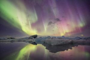 Iceland, Jokulsarlon. Aurora lights reflect in lagoon. by Josh Anon