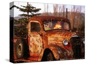 Rusty Old Truck Strung with Christmas Lights, with Santa Claus at Wheel by Judy Bellah