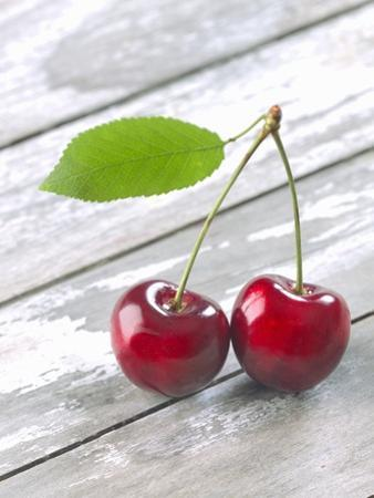 A Pair of Cherries with a Leaf on a Wooden Table by Jürgen Klemme