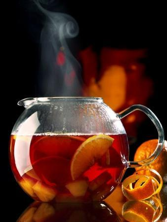 Steaming Red Wine Punch with Pieces of Fruit in Glass Teapot by Jürgen Klemme