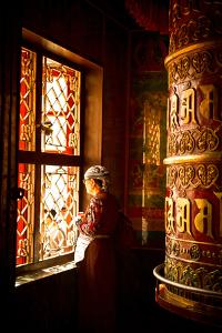 A Tibetan woman stands next to a large prayer wheel of the temple of Boudhanath Stupa, Kathmandu, N by Julian Bound
