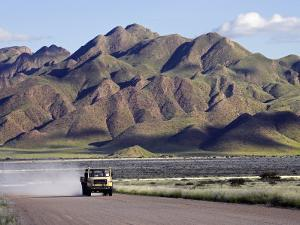 Truck Passing Through the Naukluft Mountains Near Solitaire, Namibia by Julian Love