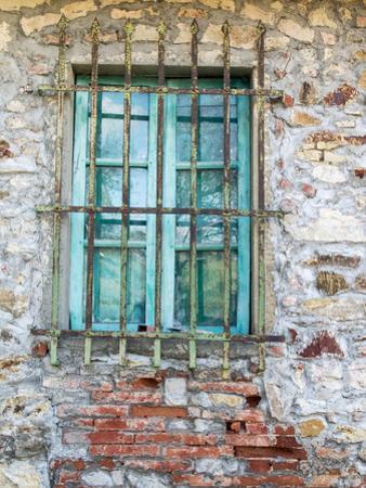 Europe, Italy, Tuscany. Turquoise Window on Brick Building