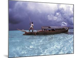 Bajau Fisherman in Traditional Lepa Boat with Rain Clouds Behind, Pulau Gaya, Borneo, Malaysia by Jurgen Freund