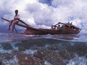 Bajau Fisherman on Lepa Boat in Shallow Water Over Coral Reef, Pulau Gaya, Borneo, Malaysia by Jurgen Freund