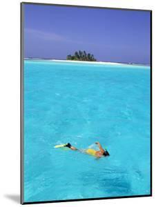 Woman Snorkelling at Sea Surface,Cocos Keeling Island in Background, Indian Ocean, Australia by Jurgen Freund