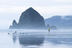 Image Of Young Woman Running On The Beach In Cannon Beach, Oregon by Justin Bailie