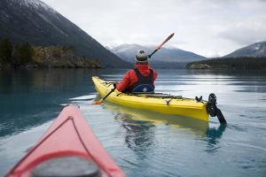 Young Woman Kayaking on Chilko Lake in British Columbia, Canada by Justin Bailie