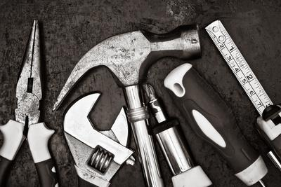 Black and White Image of a Set of Tools on a Textured Metallic Background