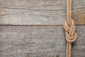 Ship Rope Knot on Old Wooden Texture Background by karandaev