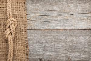 Ship Rope on Old Wood and Burlap Texture Background with Copy Space by karandaev