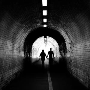 Couple walking into the light, York tunnel, York, England by Karen Deakin