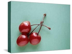 Three Cherries on a Green Background by Karen M. Romanko