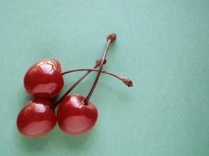 Three Cherries on a Green Background by Karen M. Romanko
