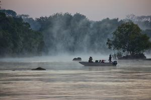 Kafue NP, Zambia. Tourist On A Boat Tour Of Kafue River Enjoys Morning Mist Before The Sun Rises by Karine Aigner