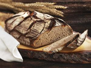 A Rustic Country Loaf on a Slice of Wood by Karl Newedel