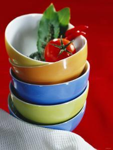 Pile of Soup Bowls with Tomato, Bay Leaf and Chilis by Karl Newedel