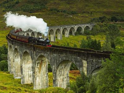 UK, Scotland, Highlands, Jacobite Steam Train crossing the Glenfinnan Viaduct.