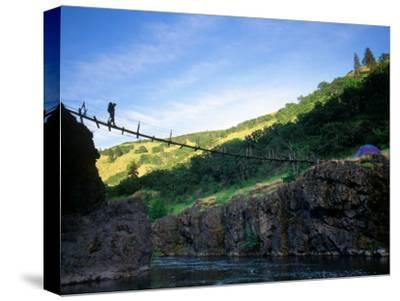 Backpacker Crosses the Bridge over the River to His Camp, Hood River, Oregon, United States