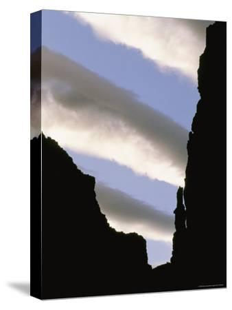 Stripes of Clouds Can Be Seen from Inside a Silhouetted Canyon