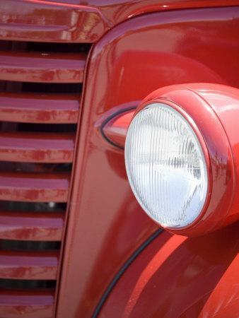 Headlight and Partial Grill of a Red Antique Truck